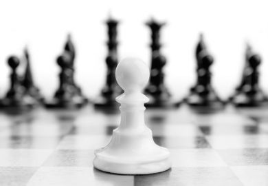 White chess pawn with black pieces in background