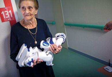 elderly woman holding robot