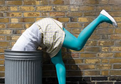 Woman diving into dustbin on street