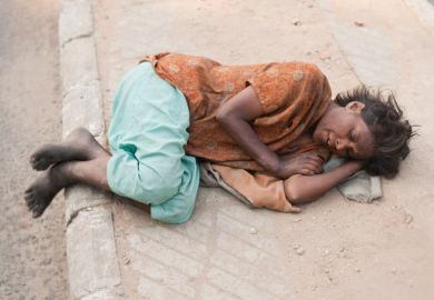 Woman lying on pavement, Delhi