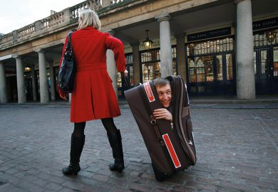 woman pulling along man hidden in suitcase