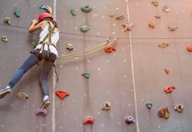 Woman representing a PhD student climbing in an indoor climbing centre