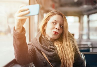 Woman taking selfie photograph with smartphone