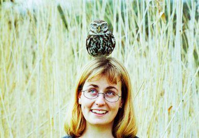 A woman with an owl balanced on her head