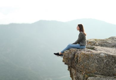 A woman sits on the edge of a cliff