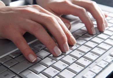 Woman's hands typing on laptop computer keyboard