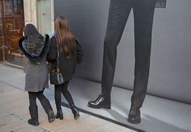 Women walking past mans legs