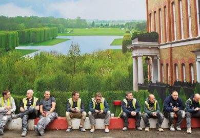 Workmen sit in front of hoarding depicting English country house and grounds