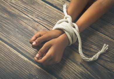 A person's wrists bound with a rope, symbolising the restriction of academic freedom