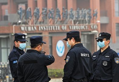 Security personnel stand guard outside the Wuhan Institute of Virology as members of the World Health Organization team investigating the origins of Covid-19 visit the institute
