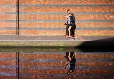 Young couple walking along canal with reflection on water