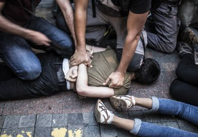 Young man pinned down on floor being arrested