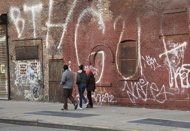 Young people walk in rundown neighbourhood