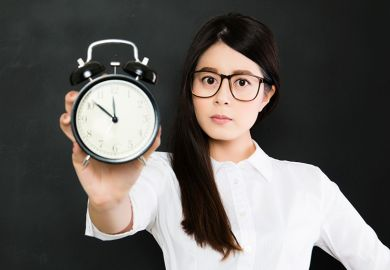 Young woman holding old alarm clock