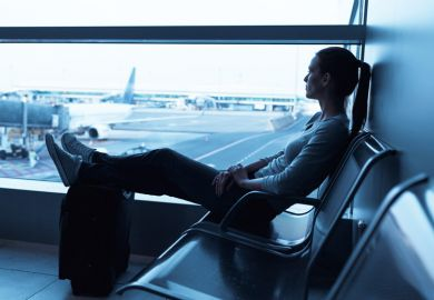 Young woman seated in airport departure lounge