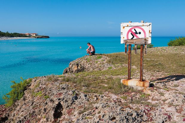 Man looking at the ocean next to a No Swimming sign
