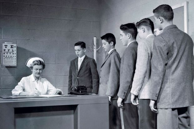 A nurse sitting at a table with a queue of people waiting to speak to her