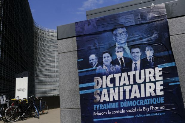 A poster of anti-vax movement in front of Berlaymont Building, the European Commission headquarters in the European district of Brussels, Belgium on April 19, 2021. stock photo