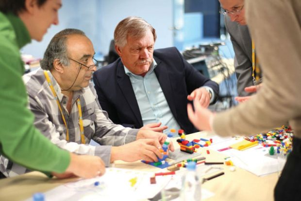 Adults playing with Lego