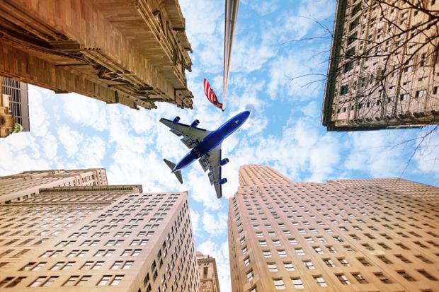 An aeroplane flies over American skyscrapers