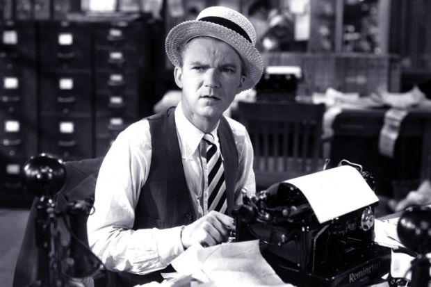 An editor sitting at a typewriter