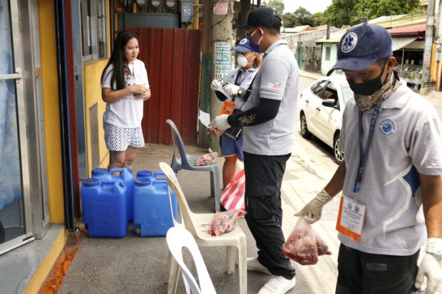 Antipolo City, Philippines - April 23, 2020 Government workers give out relief goods and put them on chairs placed in front of homes to avoid human contact during the Covid 19 virus outbreak.