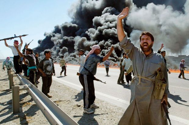 Armed Iraqi fighters standing on smoke-covered road