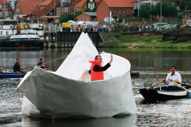 Artist Frank Boelter sitting in life-size paper boat