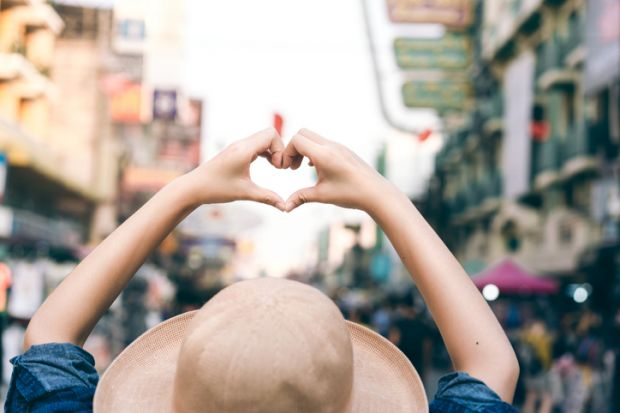 Asian traveller woman hand with heart gesture for love
