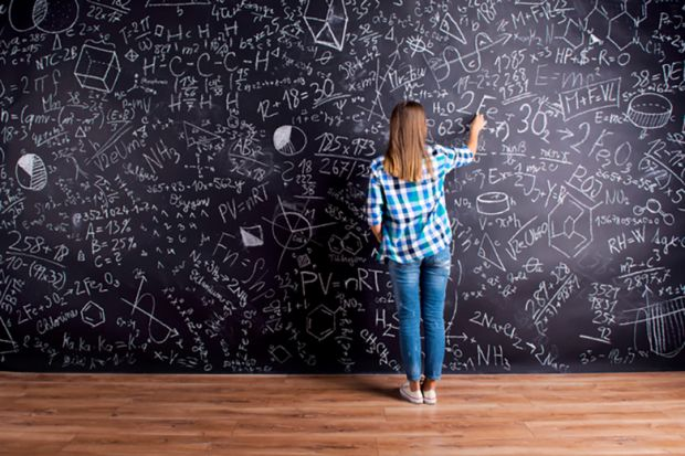 A woman writing on a blackboard that is covered in writing