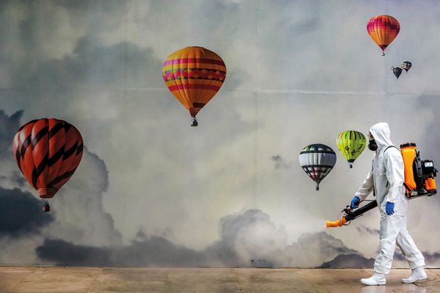 Man in PPE surrounded by hot-air balloons