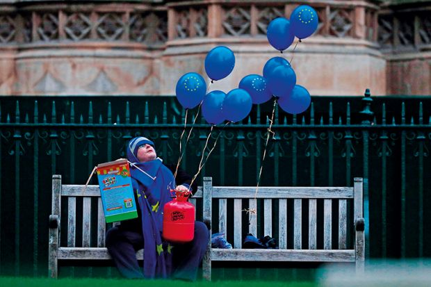 An anti-Brexit activist holds EU-flag-themed balloons outside of the Houses of Parliament in 2019 illustrating rise in university fees for EU students in England