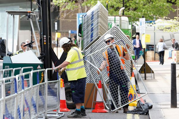 Construction workers erecting barriers