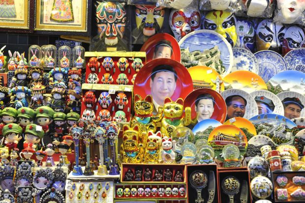 Beijing, China - October 19, 2014 - A souvenir stall at a Beijing night market selling Xi Jinping face plates and other kitsch