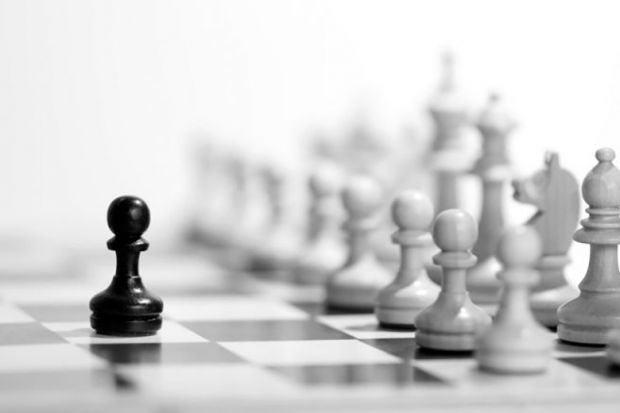 Black chess pawn in front of full set of white pieces