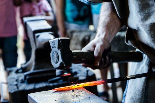 Blacksmith hammering a sword
