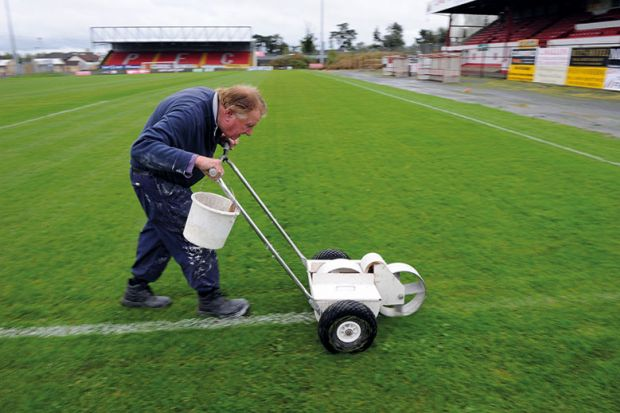Man painting lines on a pitch