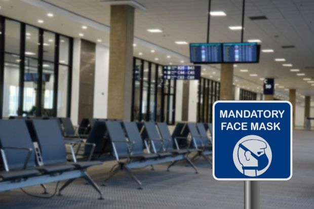 Blue sign warning that face mask is mandatory due to Covid-19 or coronavirus in airport