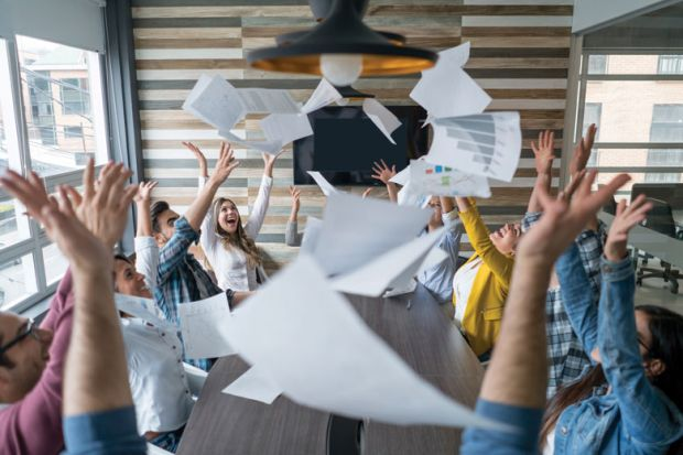Boardroom of people celebrating and throwing papers in air