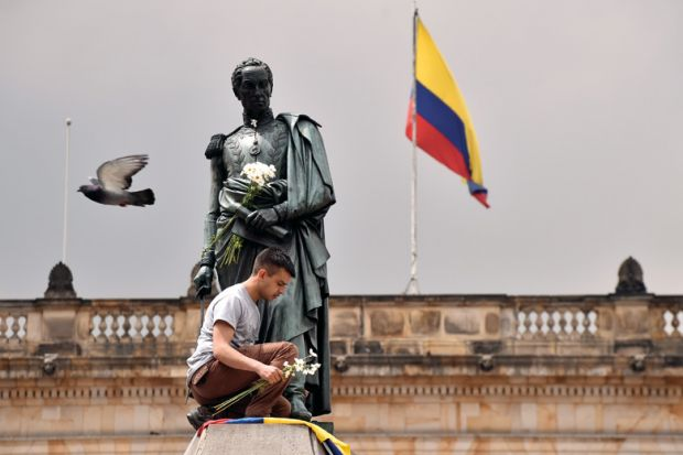 A colombian youngster places the national flag and a bunch of white flowers at the bottom of Simon Bolivar's monument in Bogota.