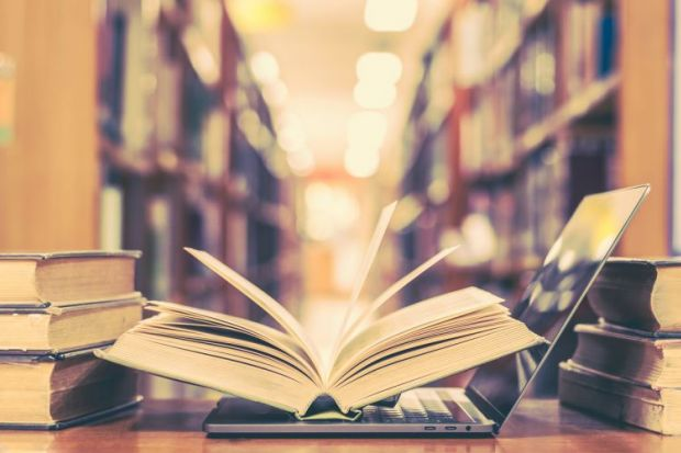 Book and laptop in library