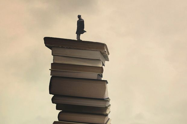 Person standing on tower of books