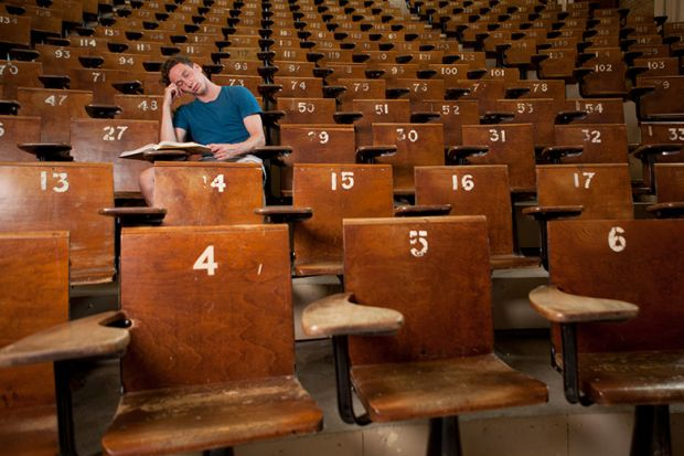 Bored student asleep in empty lecture hall