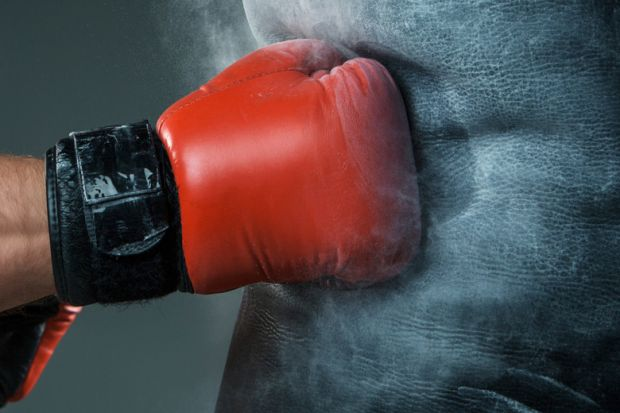 Boxer's hand punching heavy bag