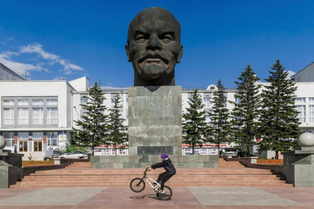 Boy riding BMX in front of bust of Vladimir Lenin