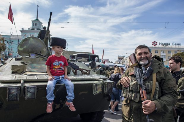 Boy sitting on armoured personnel carrier, Luhansk, Ukraine, 2014