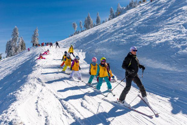 Brasov, Romania - December 10, 2018 Group of children with ski instructor on the slope in a sunny day in Poiana Brasov resort