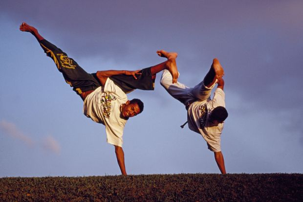 Brazilian men performing capoeira outdoors