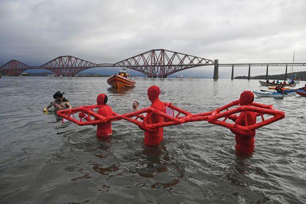 People in water pretending to be a bridge