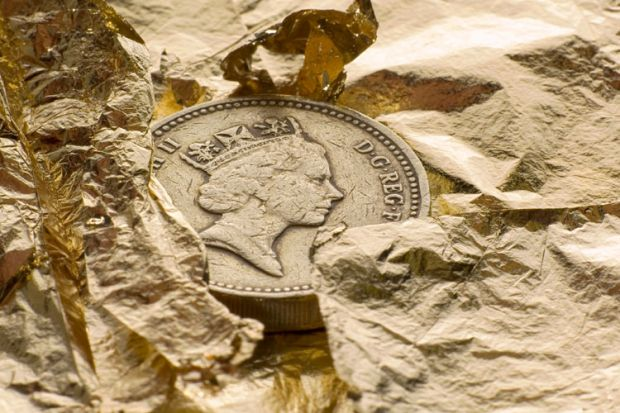 British pound coin on gold leaf